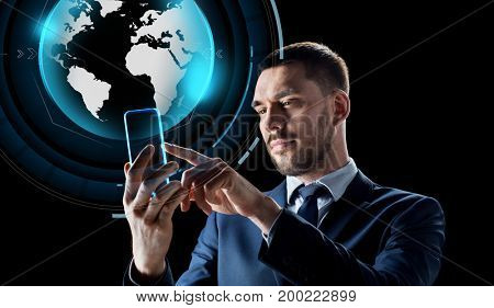 business, augmented reality and modern technology concept - businessman working with transparent smartphone and virtual earth globe hologram over black background