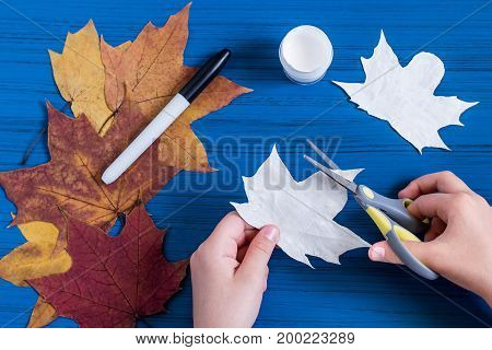 Making ghosts from maple leaves to Halloween. Halloween decor of room. Children's art project. DIY concept. Step-by-step photo instructions. Step 3. Child carves ghost