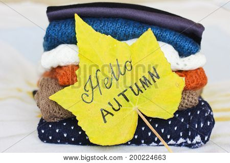 A pile of the warm sweaters and a yellow maple leaf