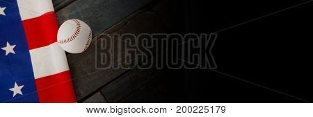 Digital composite of USA flag with a baseball ball on wood with black transition