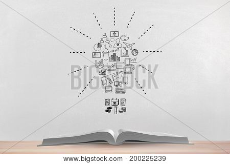 Digital composite of Book on the table against white blackboard with bulb graphic