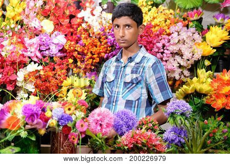 Dhaka, bangladesh, august 2017- portrait of a young man sells natural flowers at his own shops located at shavar in dhaka in bangladesh taken on 17 august, 2017.