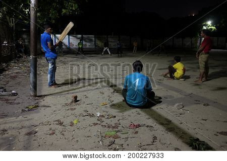 Dhaka, bangladesh, august 2017- a local group of people playing cricket under street light at local play ground llocated at shavar in dhaka in bangladesh taken on 17 august 2017.