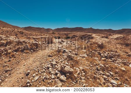 Desert Road full of stones with dune and mountains in background