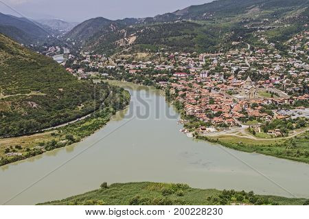 A picturesque view from the height to the first capital of Georgia Mtskheta and its buildings and to the river Terek in the afternoon among the mountains.