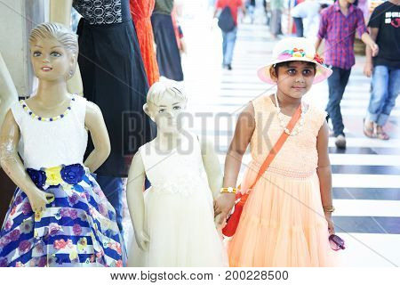 Dhaka, bangladesh, august 2017- a girl with hat is holding hand of a doll for taking pictures located at shavar shopping market in dhaka in bangladesh taken on 17 august 2017.