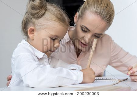 beautiful blonde mother and daughter drawing together with pencil