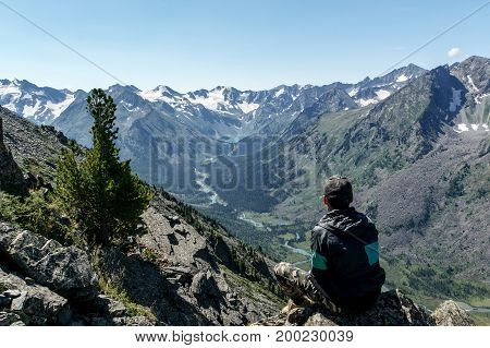 Lonely Man Looking At A River Valley Sitting On A Rock.