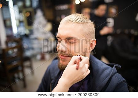 Hand of beautician putting makeup on a man. Horizontal indoors shot.