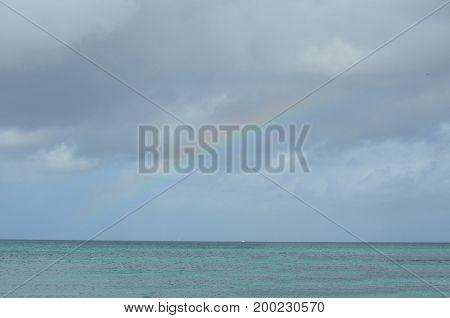 Rainbow fading into the cloudy sky of Aruba.