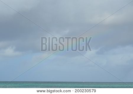 Rainbow fading across the sky in Aruba.