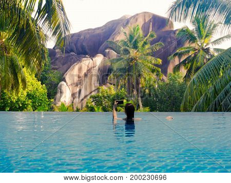 Young female in the pool on the roof on the background of Seychelles island of La Digue