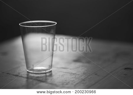 Empty Clean Backlit Plastic Cup on a Wooden Table at Night Closeup