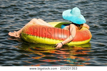 The girl is floating on a tank on the lake .