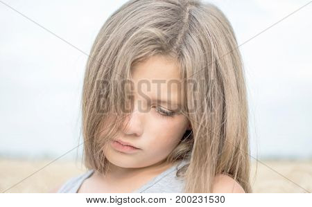 Portrait of adorable serene little girl with beautiful long hair on a summer day with blue sky and wheat field background