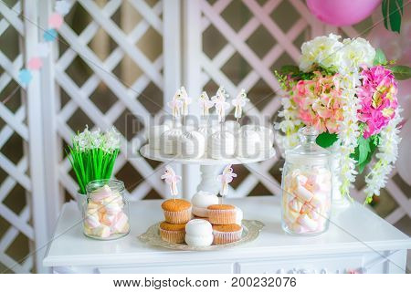 Candy bar in pink colors for a children's party. Decorated with airy bright balloons baby candy bar