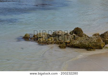 Large tumbled lava rock on the beach in Aruba.