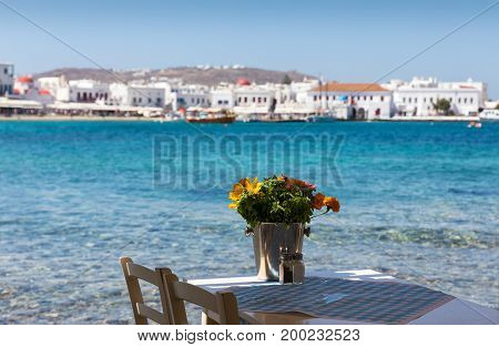 Table and flowers in front of the town of Mykonos, Cyclades, Greece