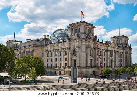 BERLIN, GERMAY - AUGUST 07, 2017: The Reichstag with many tourists in Berlin. The Reichstag is one of the most important sights of the city.