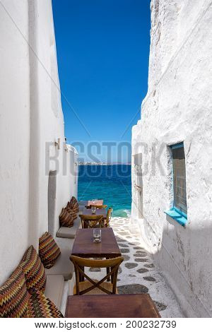 Benches and tables in a small, narrow alley facing the sea in Mykonos town, Greece