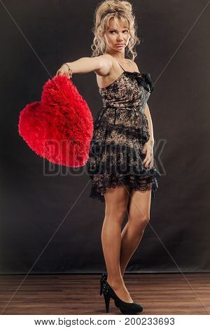 Woman middle age heartbroken female in full length wearing evening black dress holding red heart love sign studio shot on dark. Sad unhappy face expression
