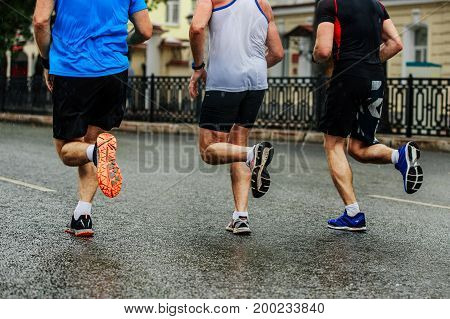 three male runners running on wet street city marathon