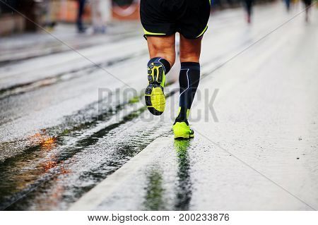 male runners in compression socks running on wet street urban marathon