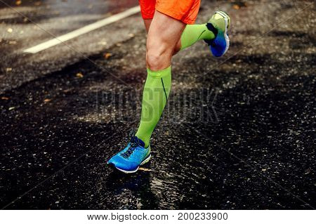 feet athlete man in compression socks running black road asphalt