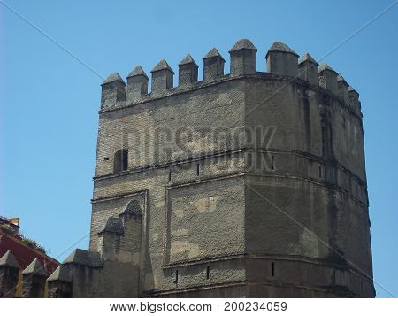 Tower of a castle in Seville on a hot summer afternoon. Tower used to defend enemy attacks throughout history.