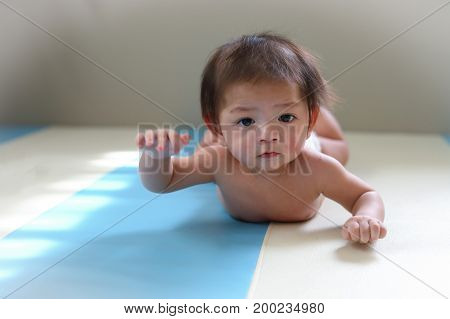 adorable baby boy trying crawl clamber first time cute asian child newborn 3 months happy relaxing in nursery room little kid new member in family home