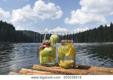 Two glass jars on a pier with infused water
