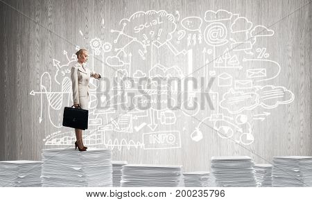 Business woman in suit standing on pile of documents with business-analytical information on background. Mixed media.