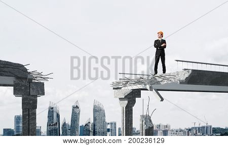 Confident engineer in helmet looking away while standing on broken bridge with cityscape on background. 3D rendering.