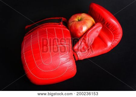 Boxing Gloves With Apple Isolated On Black Background