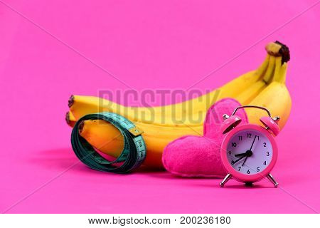 Bunch of bananas with roll of measuring tape on one of them near alarm clock and heart isolated on pink background. Concept of Valentines day and weight management
