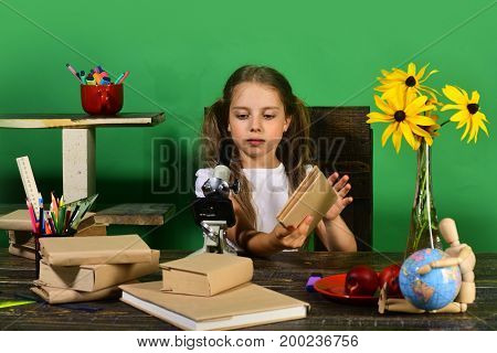 Schoolgirl With Serious Face Holds Book And Looks At Microscope