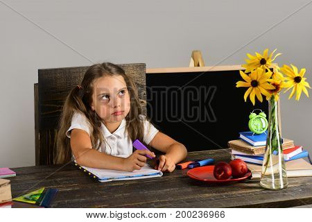 Girl Sits At Desk With Fruit, Books Stack And Flowers