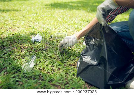 Young Man Crouching To Waste And Picking It Up In Bin Bag