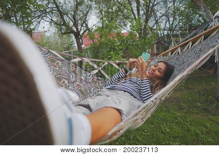 Young Mixed Race Woman Using Smartfone and Lying in Hammock in Park. Girl Chatting and Shopping Online, Using Digital Gadget