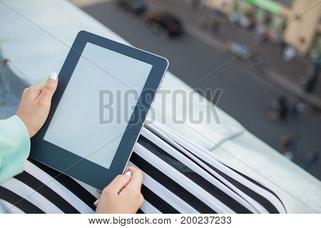 Close Up Of Female Hands With Manicure Hold An E-book. Girl Reading A Book On The Roof Of The Buildi