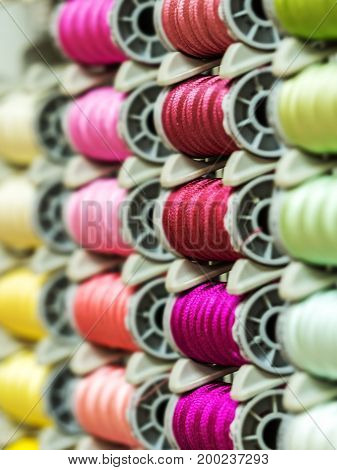 Colorful thread spools used in fabric and textile industry. Focus selection.