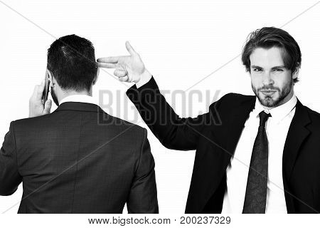 criminal business harassment diversion and sabotage corruption man with gun gesture shooting busy businessman speaking on phone in formal suit isolated on white background