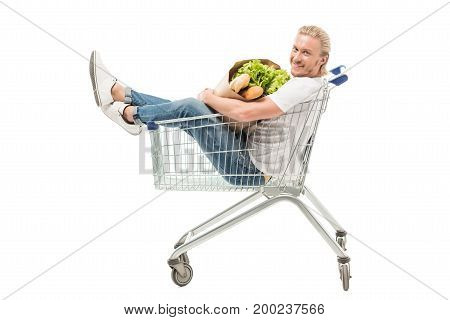 young caucasian man with paper bag sitting in shopping cart isolated on white