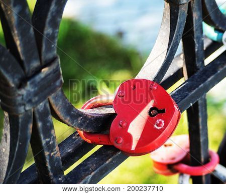 Red love lock with a heart. Fastened to a metal fence.