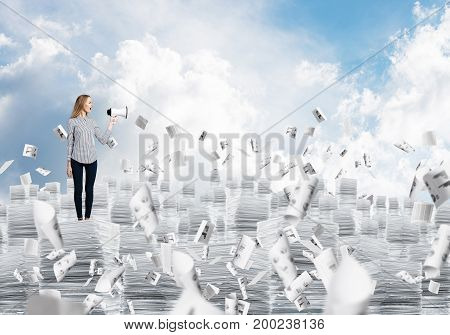 Woman in casual clothing standing on pile of documents among flying papers with speaker in hand with cloudly skyscape on background. Mixed media.