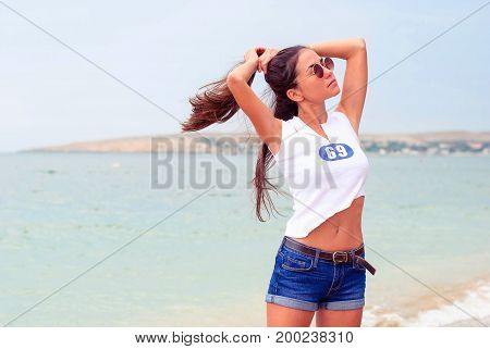 Young beautiful girl with long hair in round sunglasses of denim shorts and a short T-shirt on the beach near the sea.