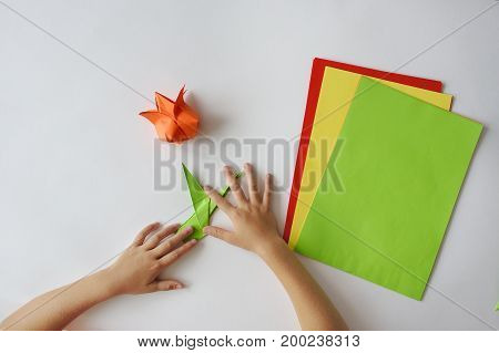 Children's hands do origami from colored paper on white background.