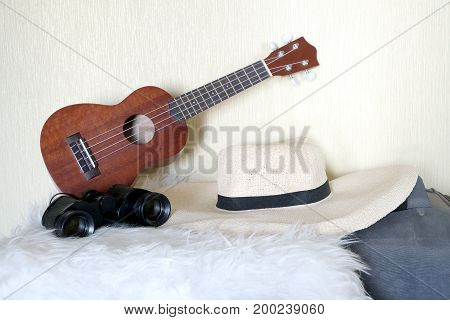 Accessories for lucky travel. guitar, straw hat, binoculars and bag