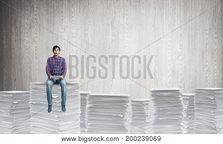 Young man in casual clothing sitting on pile of documents with grey wall on background. Mixed media.
