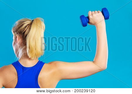 Sporty woman lifting light dumbbells weights. Fit girl exercising building muscles. Fitness and bodybuilding back view